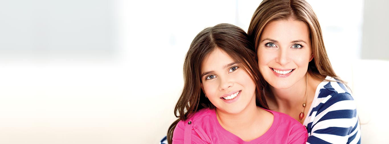 A mother with her daughter who has just received a dental filling at Sunshine Pediatric Dentistry.