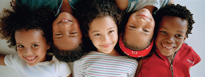 Five kids laying down smiling up at the camera