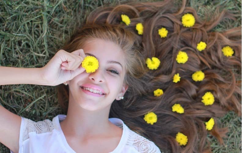 girl laying in grass flowers in hair