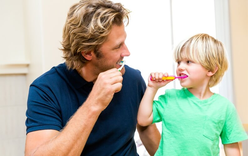 Father and son having fun brushing teeth together.