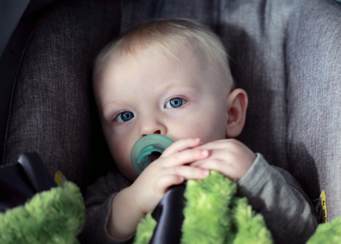 Closeup of a blonde baby boy with blue eyes in a carseat sucking on a teal pacifier and holding a green fuzzy blanket