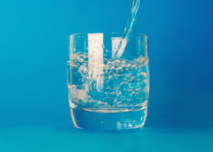 A stream of fluoridated water is being poured into a clear glass of water against a blue background