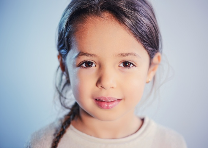 Brunette little girl with a braid and brown eyes softly smiles against a gray blue background