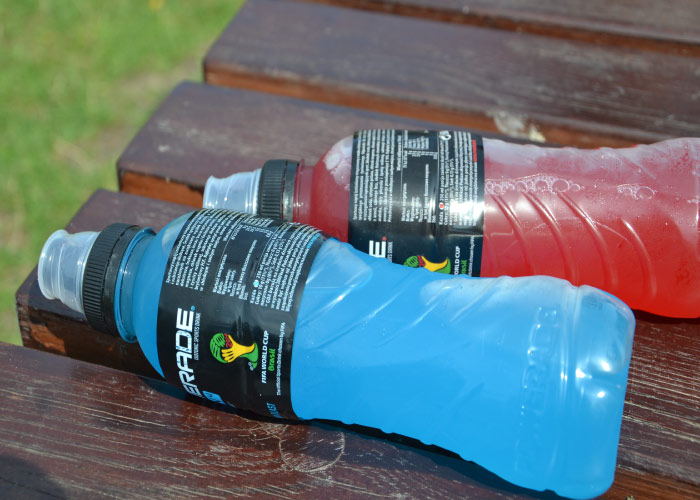red and blue bottles of sports drinks with sugar lay on a brown bench outside by the grass