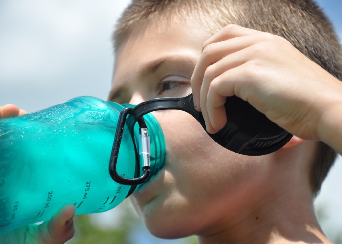 A blonde young boy drinks ice cold water from a turquoise water bottle outside while playing
