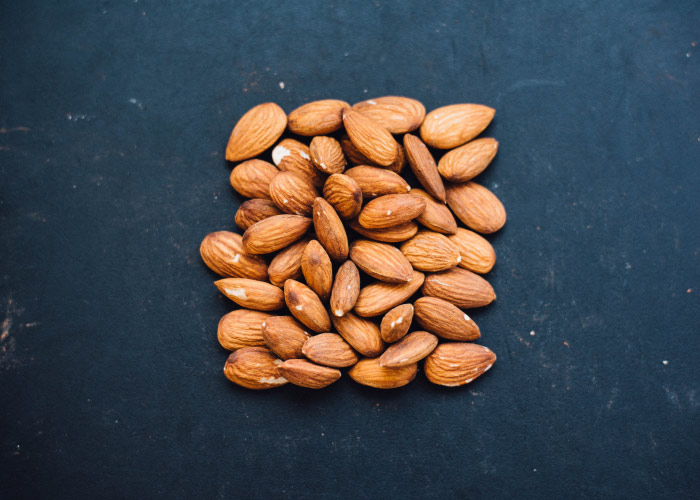 Aerial view of a cluster of smile-friendly almonds arranged in a square on a dark blue counter for lunch