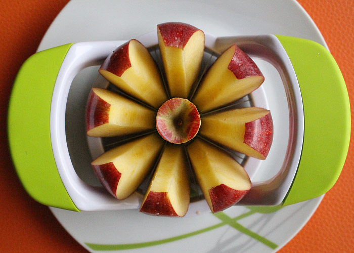 Aerial view of an apple sliced into 8 pieces with an apple corer and slicer for lunch