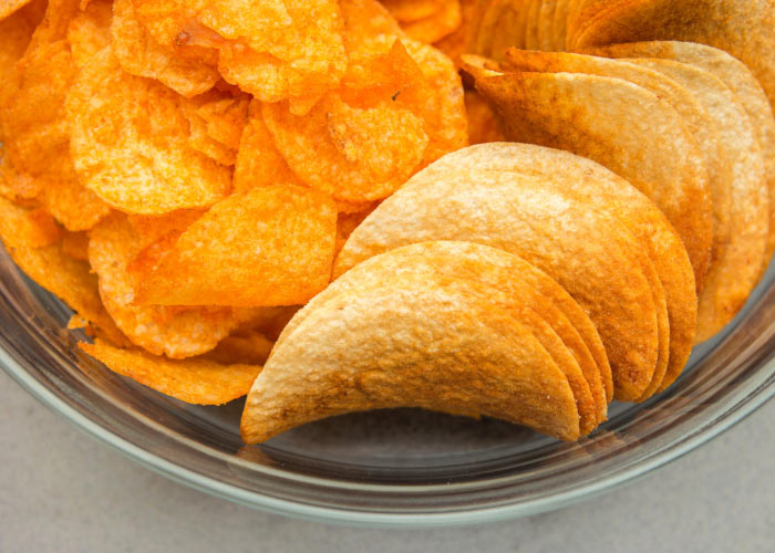 Closeup of a cluster of orange potato chips that are unhealthy for teeth