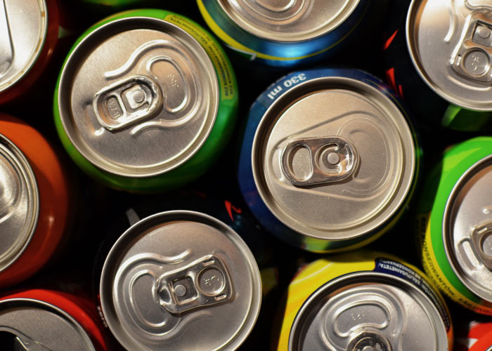 Aerial view of aluminum soda cans with carbonated soda that damages teeth
