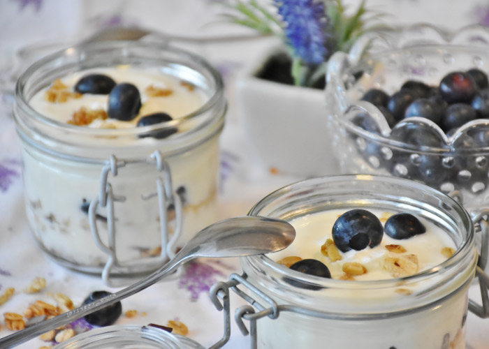 Closeup of 2 glass containers full of smile-friendly yogurt and blueberries for lunch