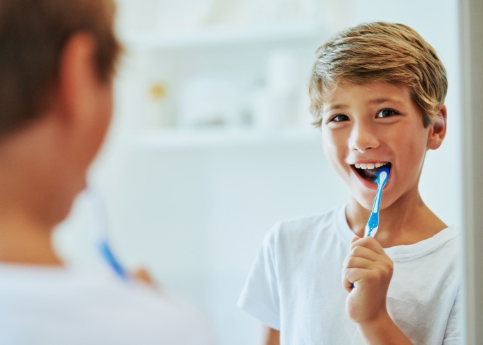 Brunette boy brushes his teeth with a blue toothbrush and toothpaste while looking in the mirror