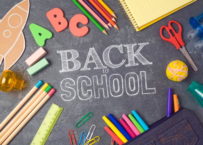 Aerial view of a black chalkboard with the words BACK TO SCHOOL surrounded by various colorful school supplies