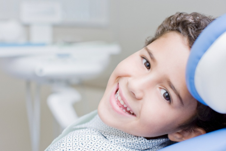 Smiling dark eyed boy looking sideways from the dental chair