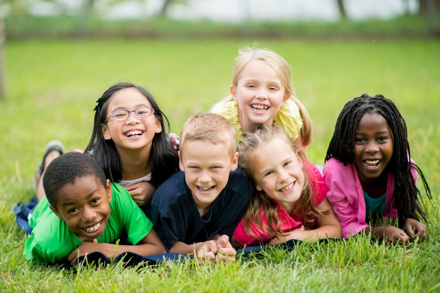 Six multicultural smiling kids on the grass