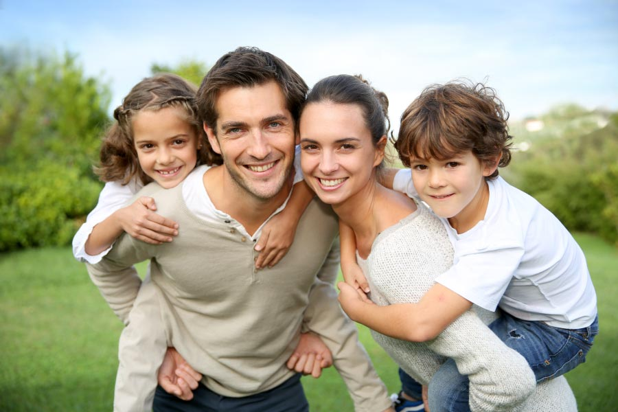 Young smiling family with girl on dad's back and boy on mom's back