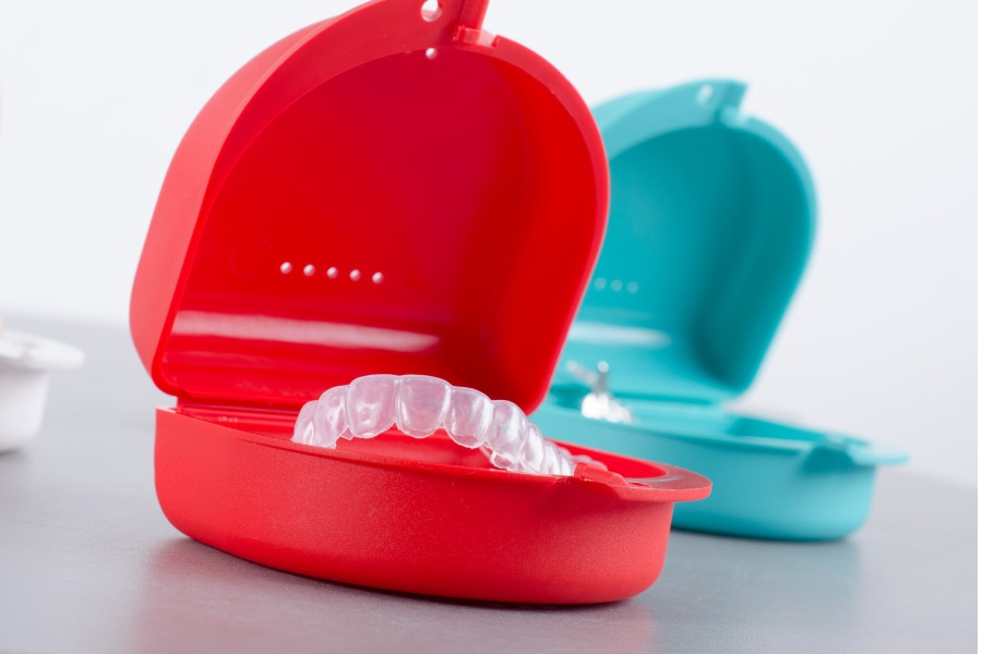 Invisalign clear aligners in bright orange and turquoise cases