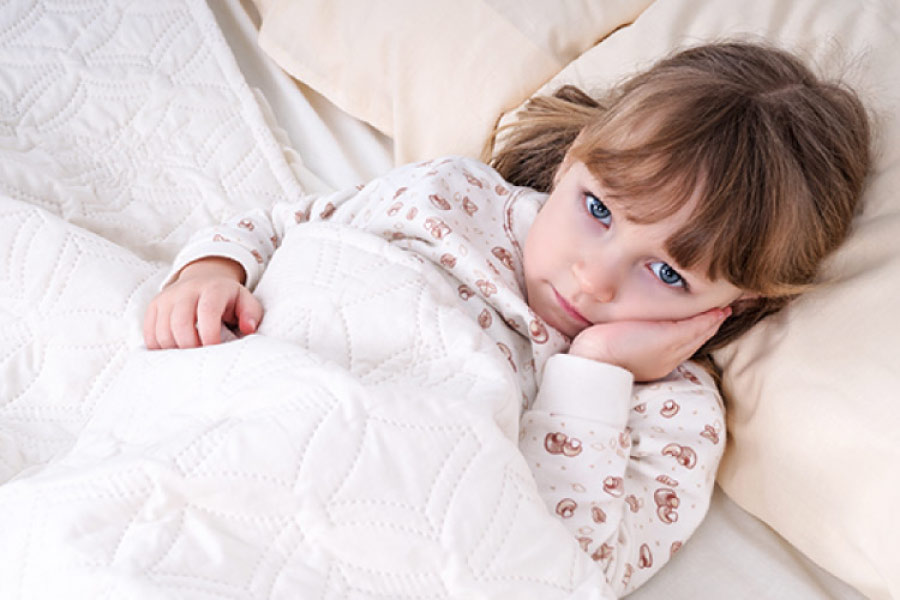Little girl resting in bed with her hand on her cheek indicating a toothache.