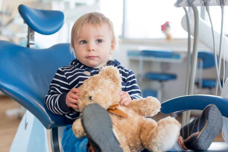 Blond toddler boy in the dental chair with his teddy bear.