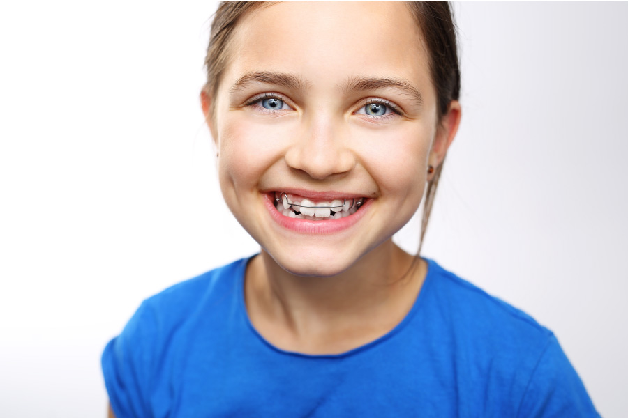 Young smiling girl with early intervention braces on her teeth.